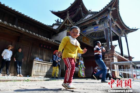 儿童在沙溪古镇戏台前跳舞。 任东 摄